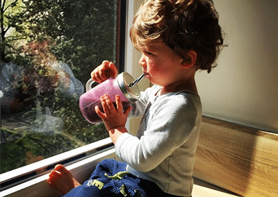 child drinking fresh fruit smoothie